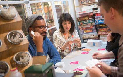 Four adults play cards, with a pile of board games behind them.